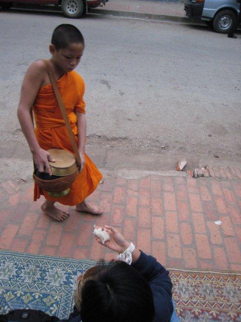Luang Prabang, young monk receiving food